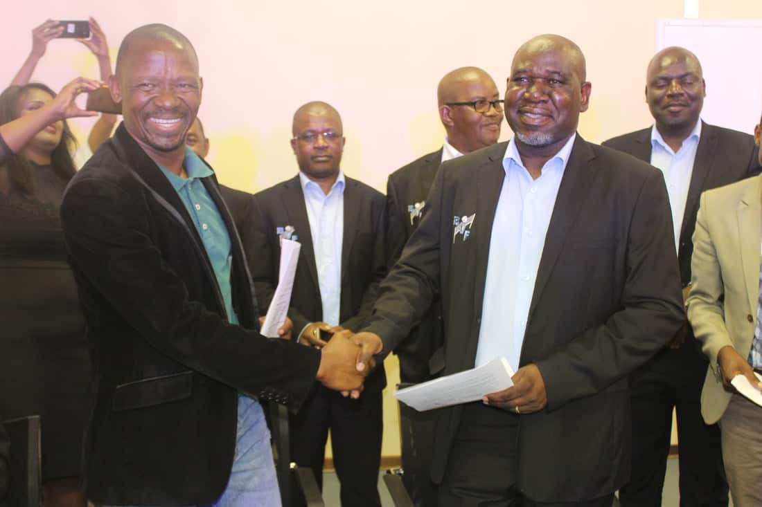 Baboneng Film boss Mr Seabelo(L) and Volleyball boss shaking hands after signing off a historic partnership